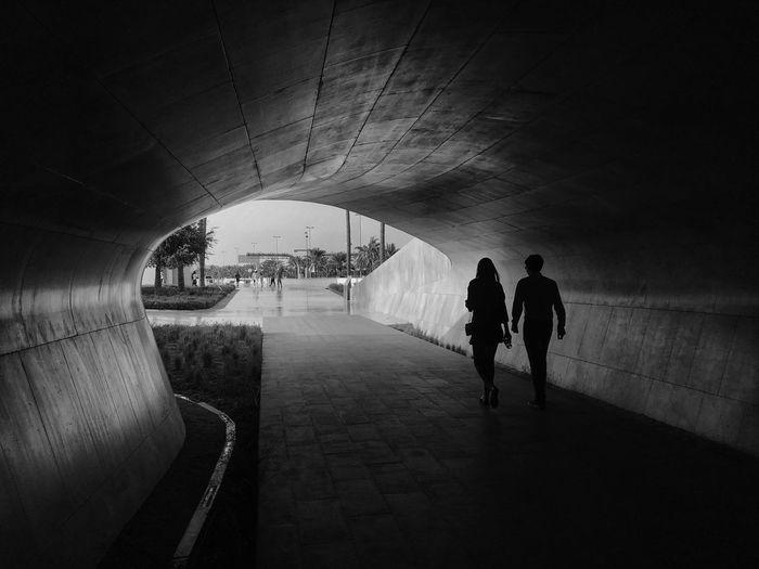 Rear view of silhouette people walking on footpath in tunnel