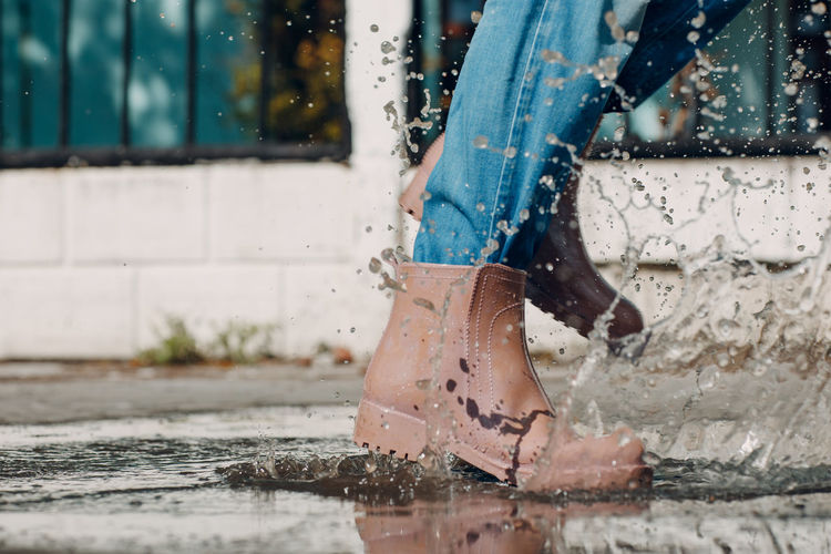 Low section of woman with wet umbrella in rainy season