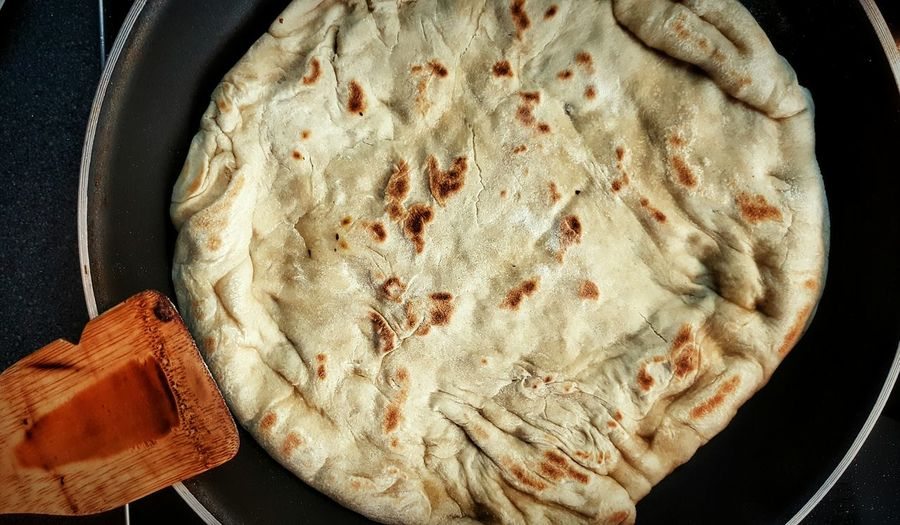 High angle view of pizza bread in cooking pan at home