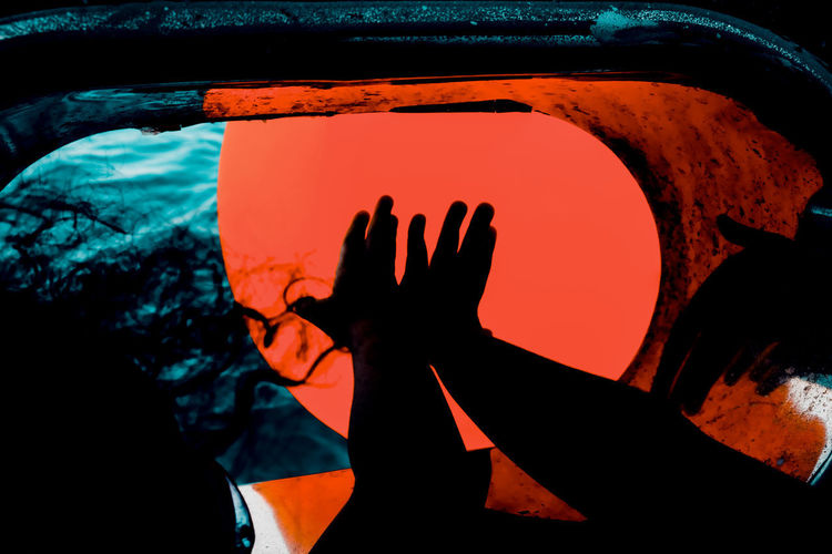 Close-up of silhouette hand against orange sky