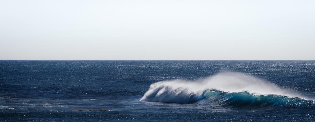Waves splashing on sea against clear sky