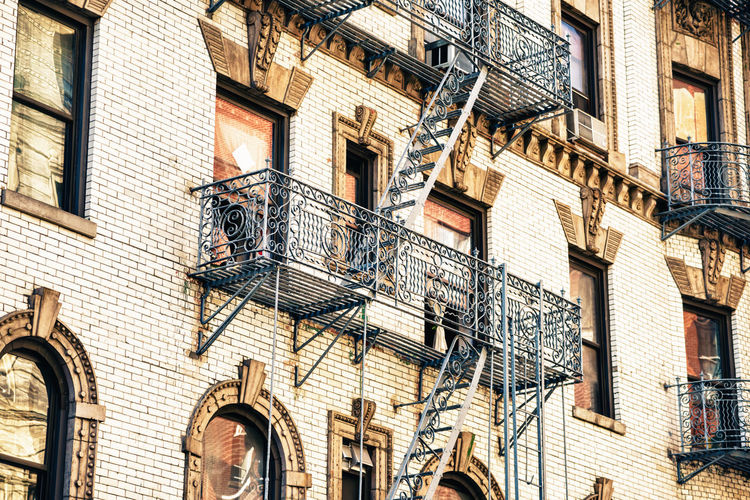 Crop shot of building with emergency stairs. Apartment Architecture Backgrounds Balcony Brick Building Building Exterior Built Structure City Day Fire Escape Full Frame Lifestyles Low Angle View No People Outdoors Railing Residential District Street Wall Window