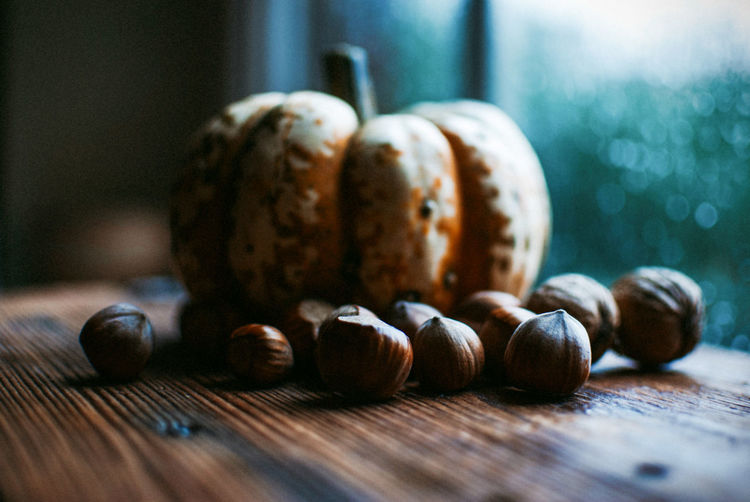 Close-up of chestnuts and pumpkin on wooden table by window