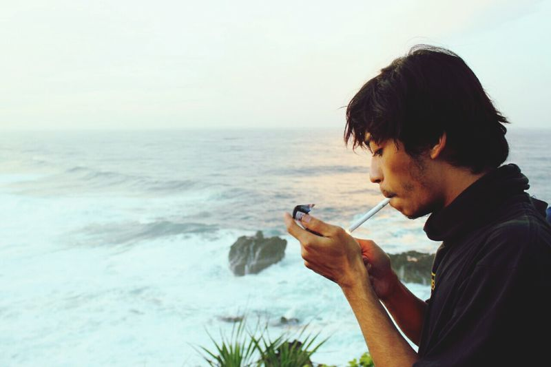 Side view of young man smoking while standing at beach against sky