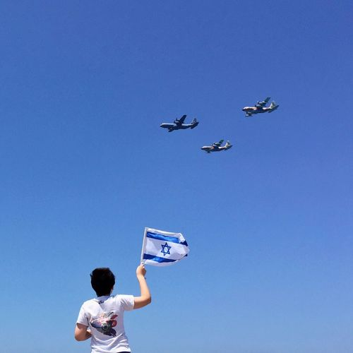 Low angle view of boy with israeli flag looking at airplane against sky