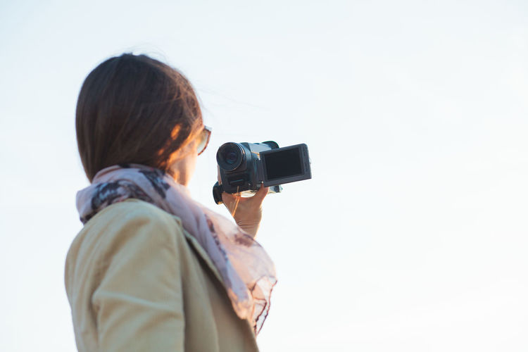 Rear view of woman photographing against clear sky