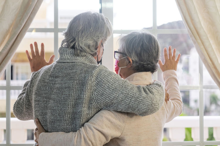 Rear view of senior couple wearing mask looking through window at home