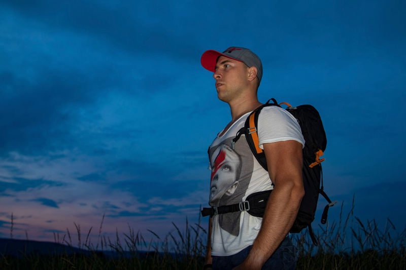 Man with backpack looking away while standing on field against sky during sunset
