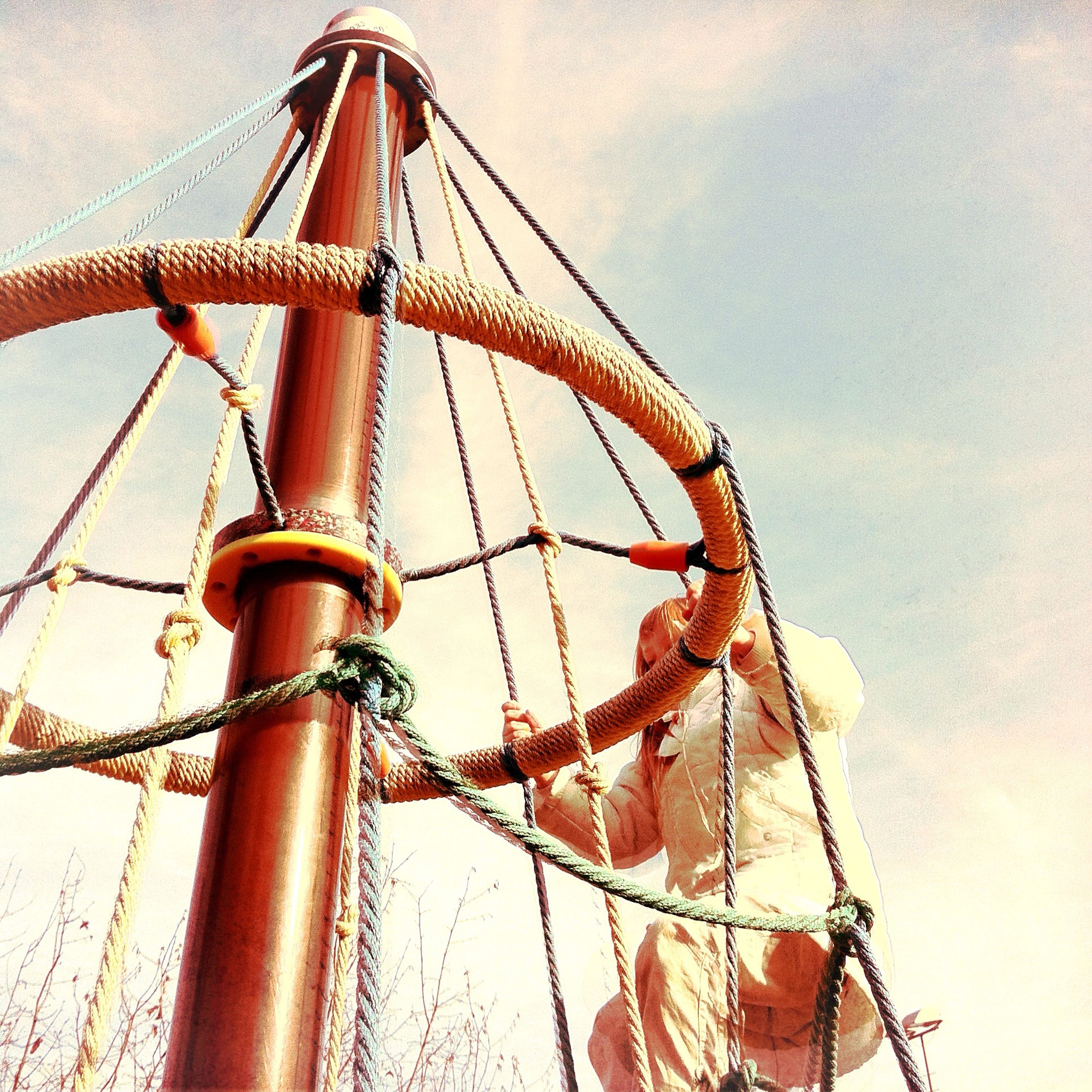 low angle view, sky, arts culture and entertainment, amusement park, metal, amusement park ride, rope, red, metallic, ferris wheel, outdoors, day, built structure, part of, nautical vessel, no people, protection, development, architecture, mast