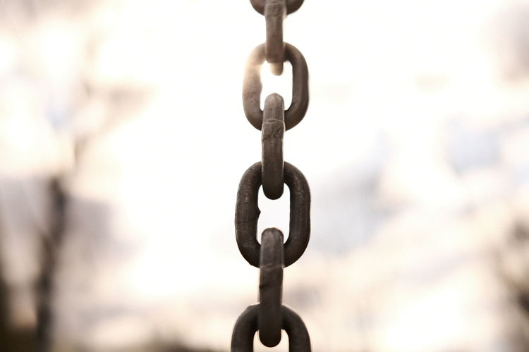 Close-up of metal chain against sky