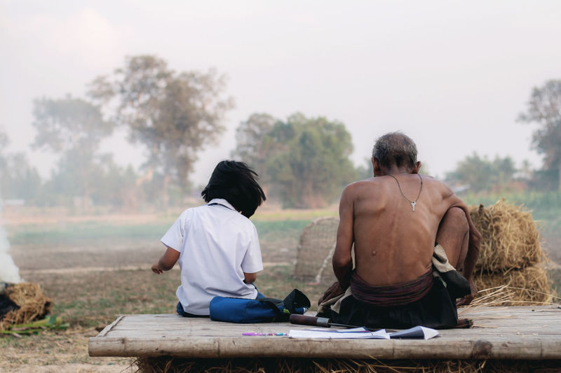 Rear view of people sitting on landscape against sky
