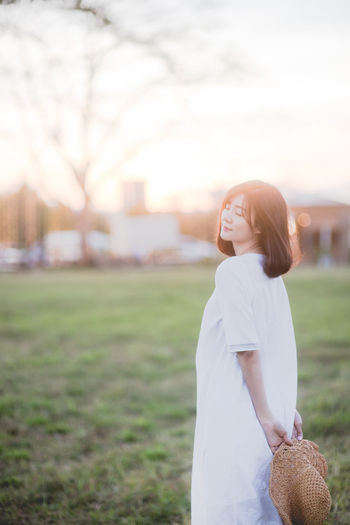 Side view of woman with eyes closed standing on field against sky during sunset