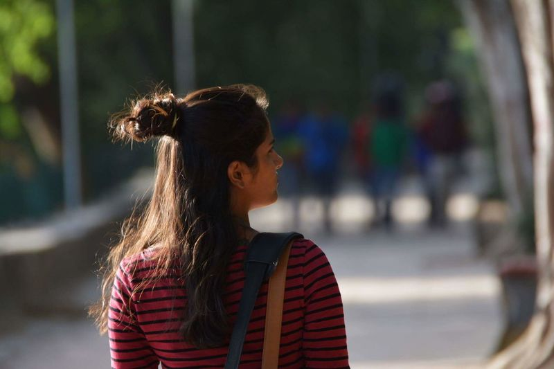 Rear view of young woman on footpath at park