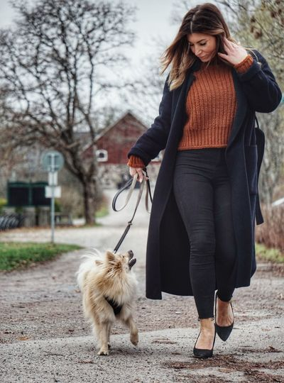 Woman walking dog on street against sky