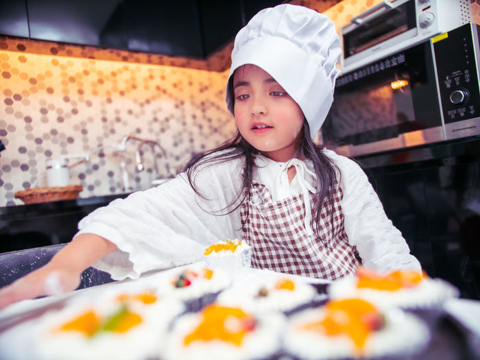 Cute girl wearing chef hat and apron while preparing food in kitchen