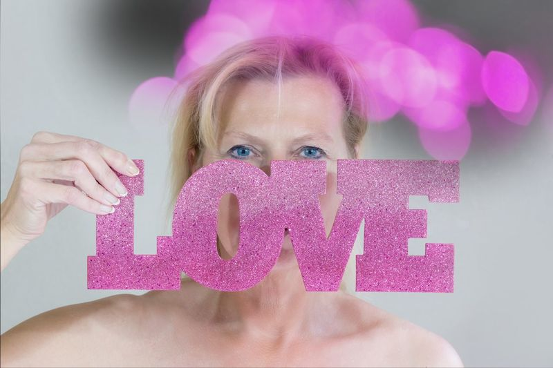 Portrait of woman holding love text