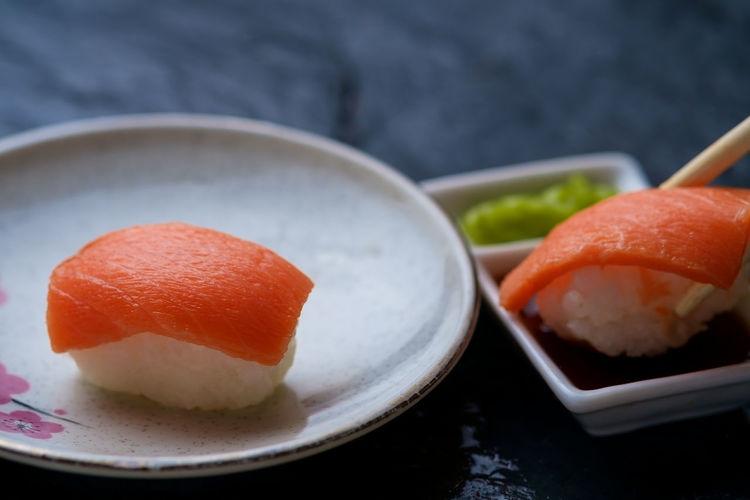 Close-up of sushi in plate by soya sauce on slate