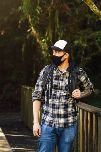 Man wearing mask standing in forest