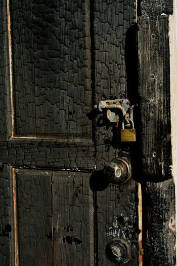 blackened fire-charred wooden door found in Mexico Burned Door Abandoned Blackened Burned House Charred Charred Wood Close-up Closed Day Door Entrance Fire-charred Latch Lock Metal No People Old Outdoors Protection Safety Security Textured  Wall - Building Feature Weathered Wood - Material