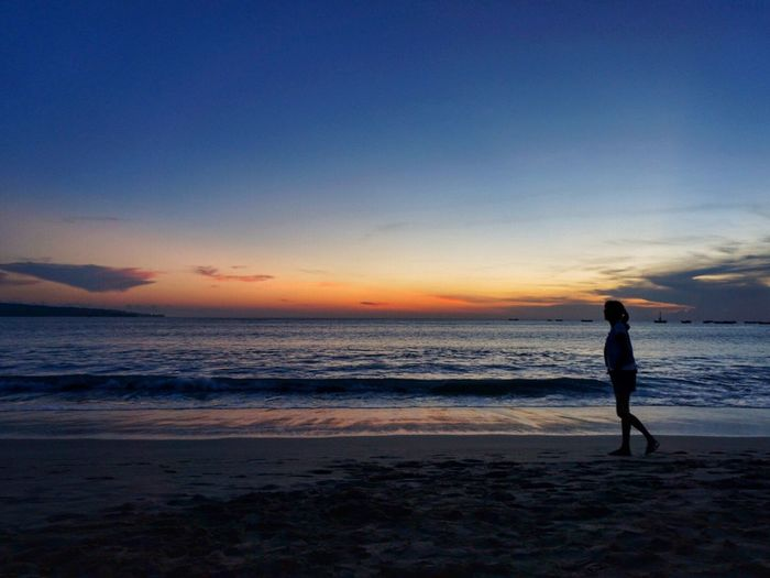 Silhouette woman walking on beach against sky during sunset