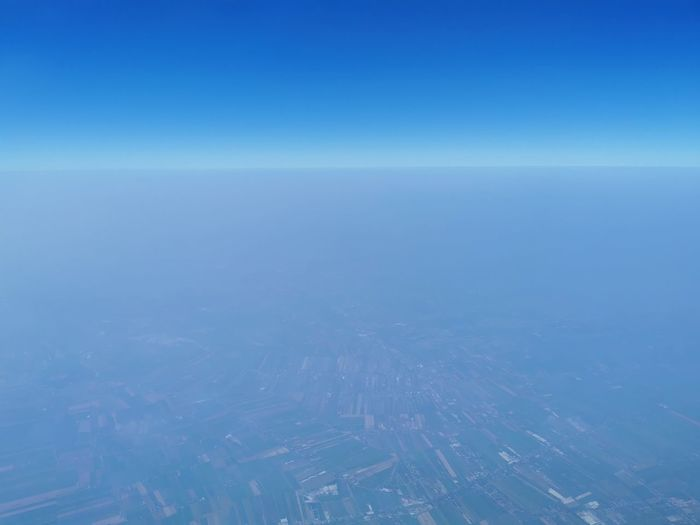 Aerial view of sea against clear blue sky