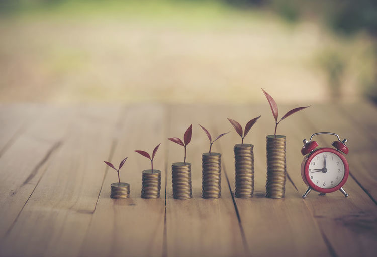Stacked coins with leaves and alarm clock on table