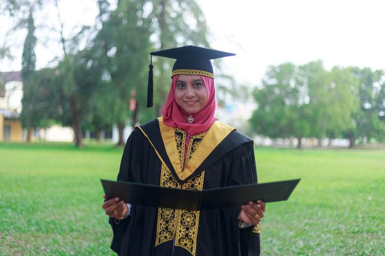 Portrait of woman in graduation gown standing on field