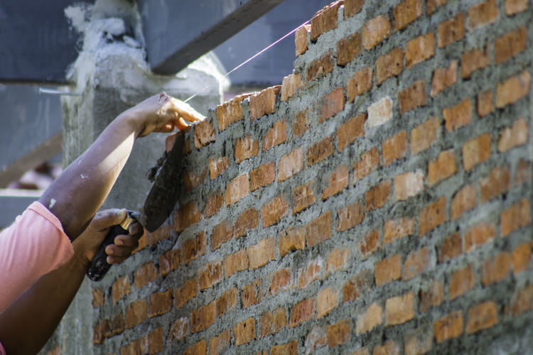 Cropped image of worker constructing wall