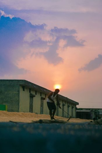 Surface Level Image Of Young Man Digging On Field Against Sky During Sunset