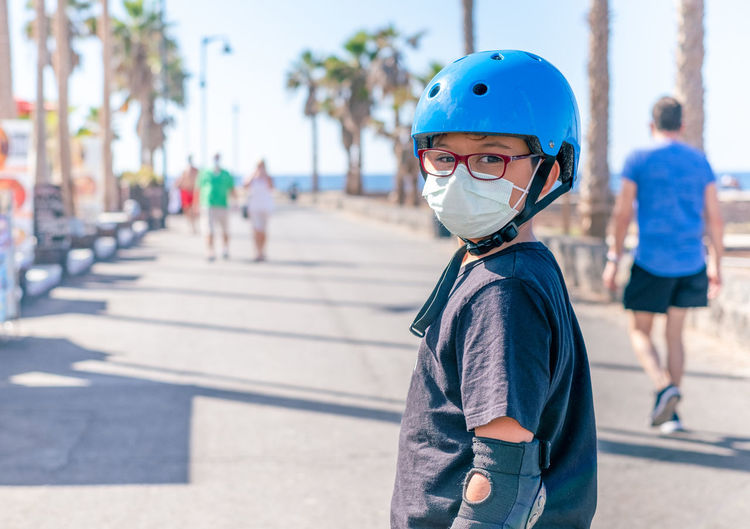 Portrait of boy wearing mask and helmet standing on road