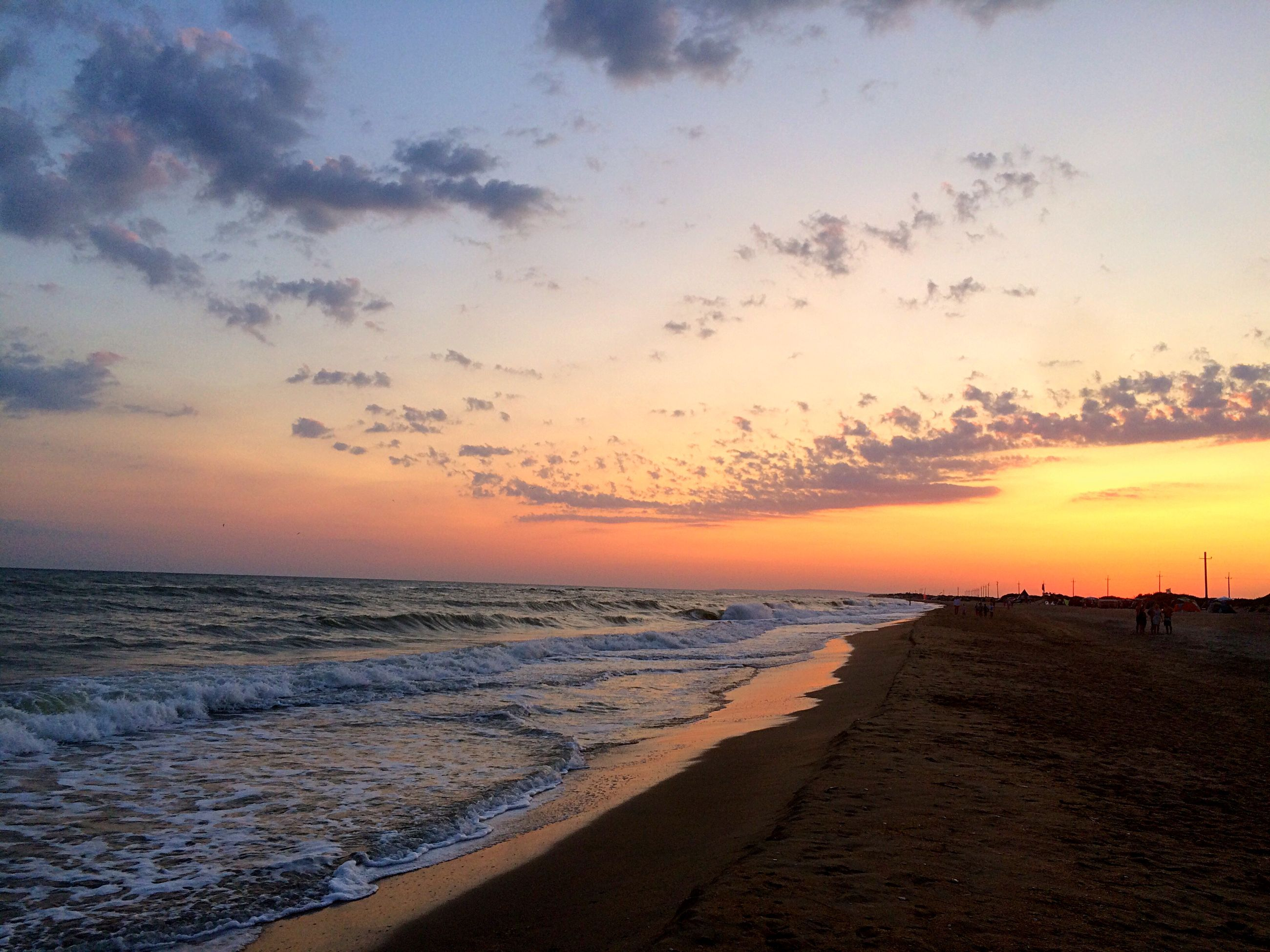 sea, beach, horizon over water, sunset, water, scenics, shore, tranquil scene, sky, beauty in nature, tranquility, sand, orange color, nature, idyllic, wave, cloud - sky, coastline, silhouette, incidental people