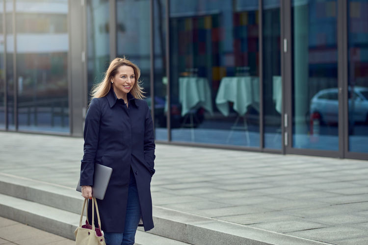 Copy Space Happy Woman Business Person Businesswoman Candid Career Front View Laptop Middle-aged Office Building One Person Outdoors Portrait Real People Smiling Standing Urban Walking