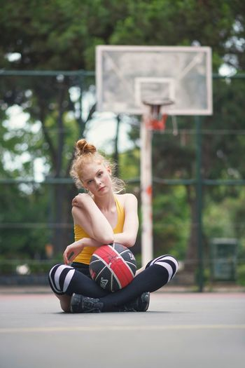 Portrait of young woman sitting with basketball at sports court