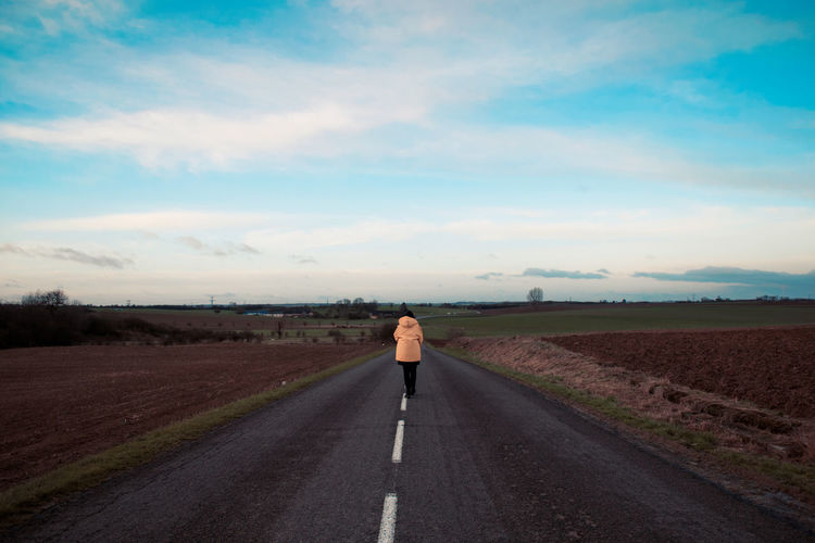 Rear view of woman walking on country road against sky