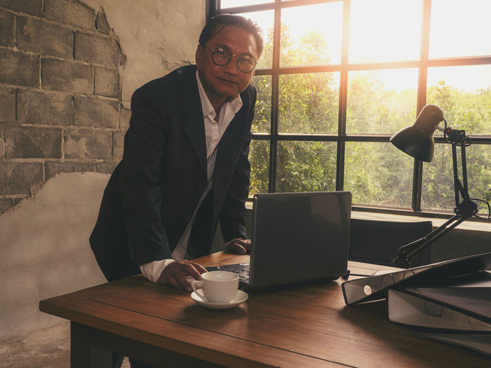 Businessmen who are diligent for business success are using laptop computers for Internet communication. One Person Table Adult Senior Adult Men Males  Real People Window Drink Indoors  Waist Up Cup Sitting Food And Drink Eyeglasses  Senior Men Communication Mug Wireless Technology Mature Men