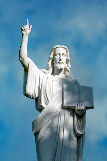 a beautiful statue of Jesus holds a stone bible and points up towards heaven Christian Christianity Christmas Heaven Jesus Architecture Art And Craft Blue Book Craft Creativity Day History Human Representation Male Likeness Nature Religion Representation Sculpture Sky Skyscraper Spritualism Statue The Past Uplifting