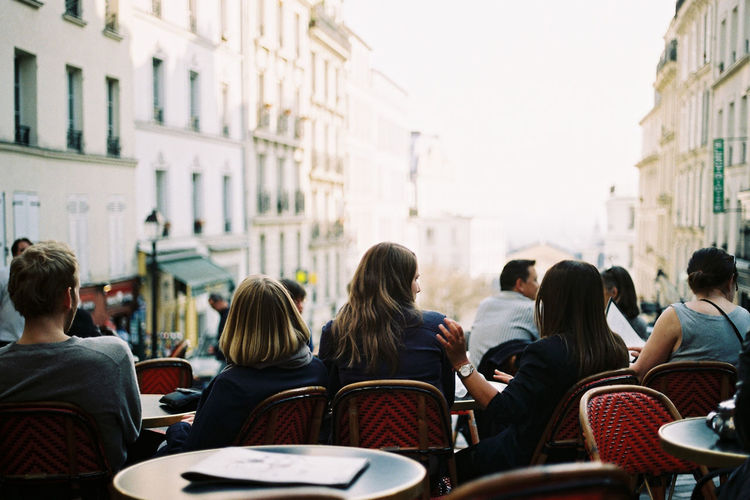 Rear view of people sitting at outdoor cafe in city