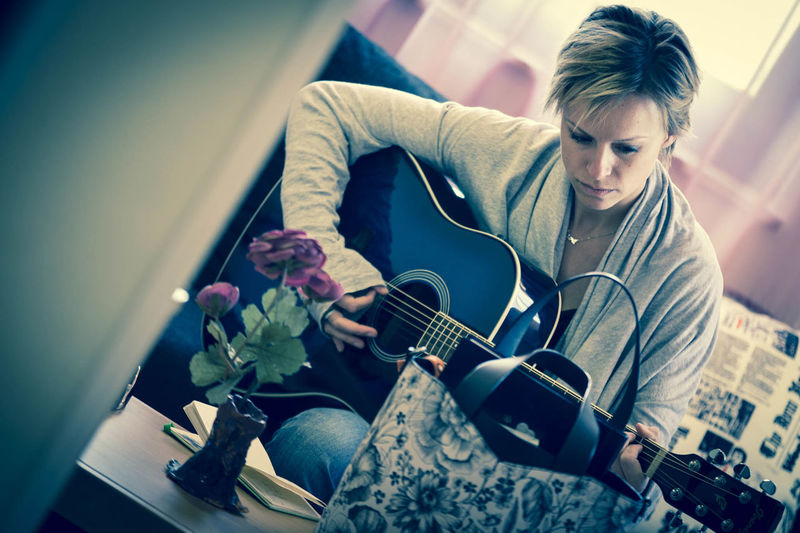 Woman with short hair playing guitar at home