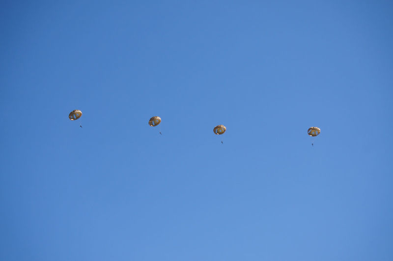 Low Angle View Of Parachutes Against Clear Blue Sky