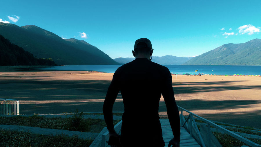 Rear view of man looking at sea against mountains