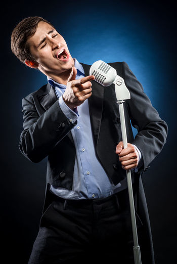 Opera singer singing while standing against black background