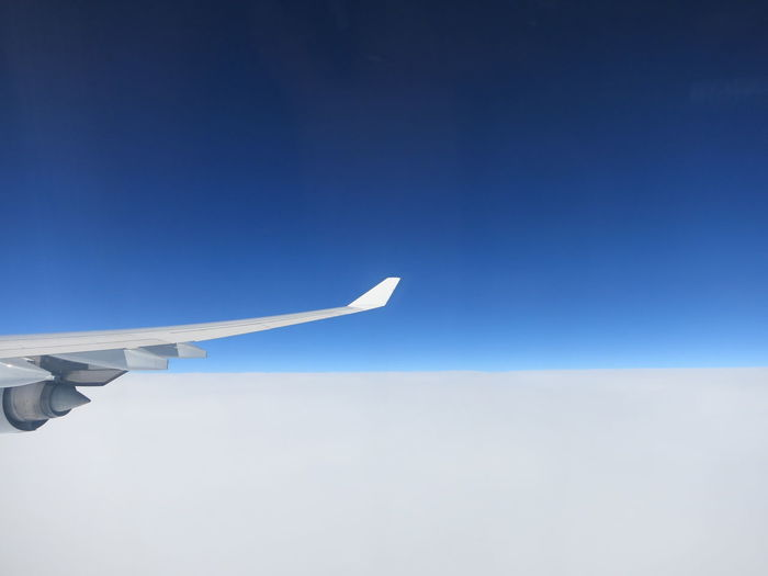 Airplane wing against clear blue sky