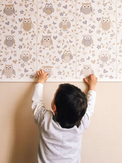 Rear view of child standing against patterned wall