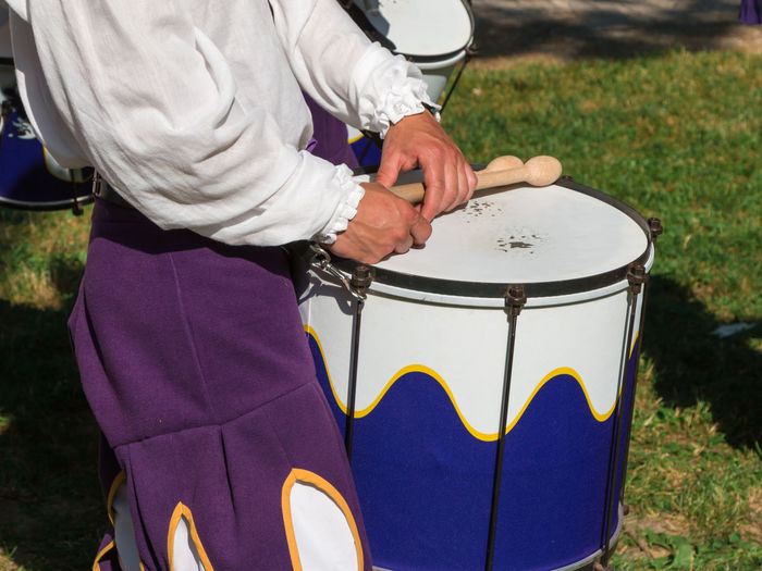 Midsection of man playing drum while standing outdoors