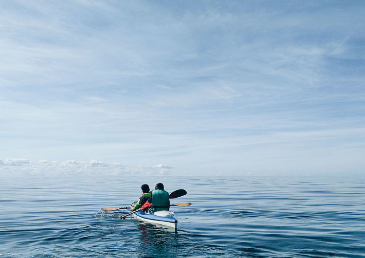 Rear View Of Friends Kayaking On Sea Against Sky