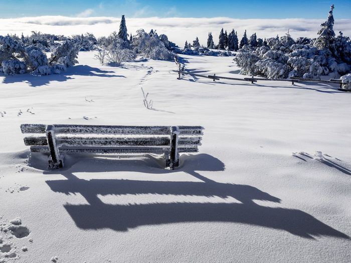 Snow Covered Park Bench On Field Against Sky