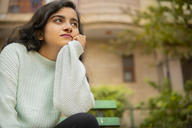 Portrait of young woman looking away while sitting outdoors