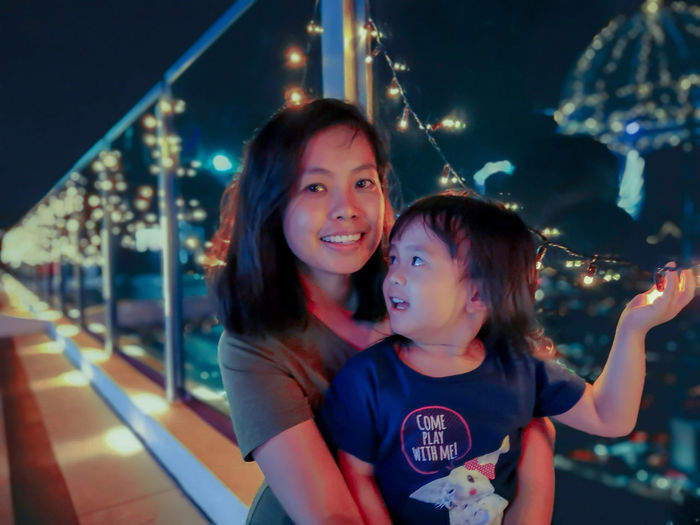 A young asian woman with her daughter pose with blur bokeh background Fairy Lights Family Time Family Time Night Blur Background Bokeh Blue Hour Neon Style Cuddling Cute Love Child Illuminated City Females Childhood Smiling Togetherness Girls Time Family Bonds