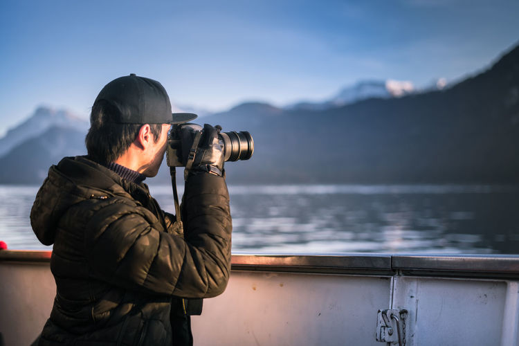 Side view of man photographing sea with digital camera