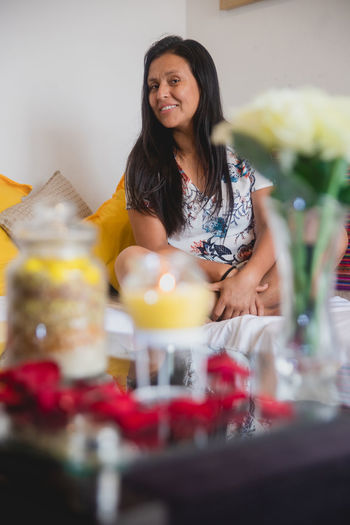 Smiling young woman with drink on table